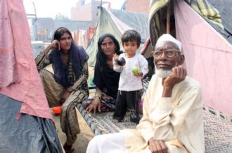 Sham Shamsad, 69 (right), sits with his daughter Naima, 18 (far left)  [Sonia Paul/Al Jazeera]