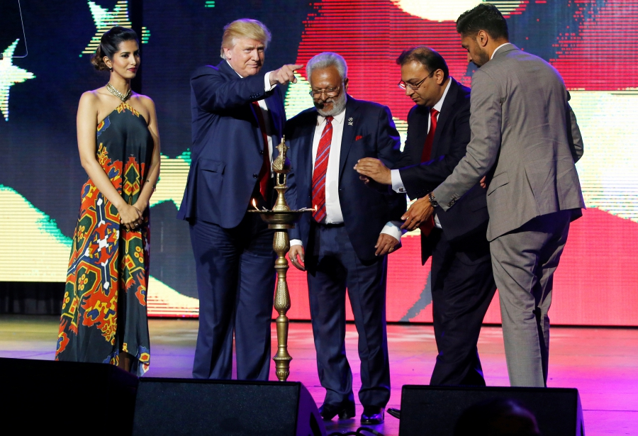 Republican Hindu Coalition Chairman Shalabh Kumar, center, stands with Republican presidential nominee Donald Trump to light a ceremonial diya lamp before he speaks to a crowd at a charity event hosted by the Republican Hindu Coalition in New Jersey. Credit: Jonathan Ernst/Reuters