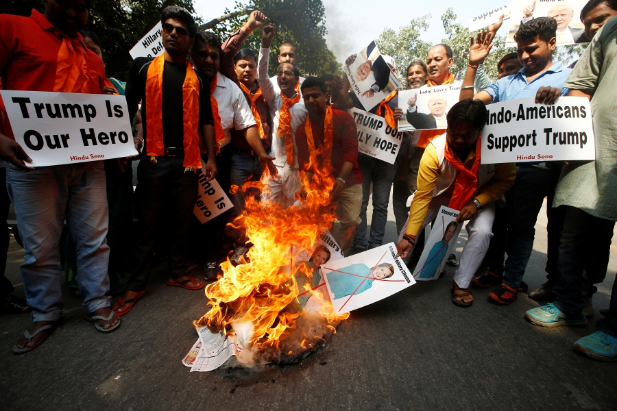 Members of Hindu Sena, a right wing Hindu group in India, burn posters of US Democratic presidential nominee Hillary Clinton during a protest against what they say is Clinton sabotaging Republican US presidential nominee Donald Trump's election campaign, in New Delhi, on October 18, 2016. Credit: Adnan Abidi/Reuters